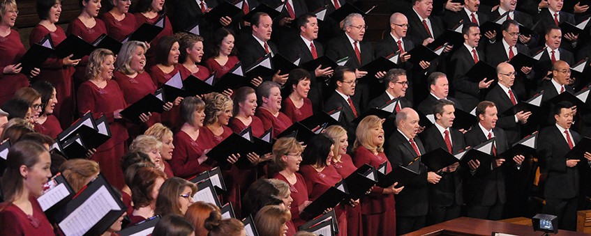 A choir of men and women singing at a concert.