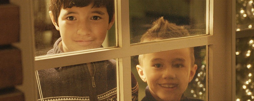 Two young boys staring out a window, smiling.